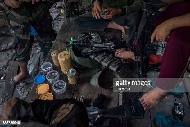 Moro Islamic Liberation Front Fighters and local police examine improvised explosives captured from extremists at the frontline of battle on August...
