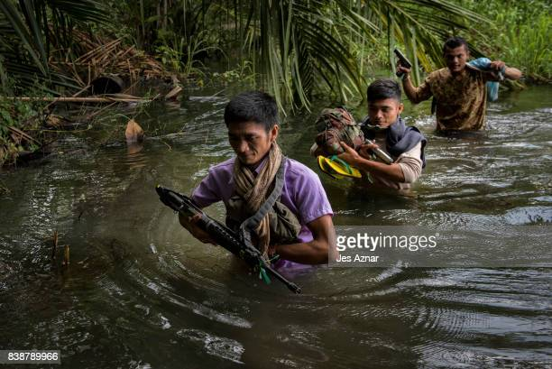 Moro Islamic Liberation Front Fighters and local police walk through a marshland on their way to the frontline of battle against extremists on August...