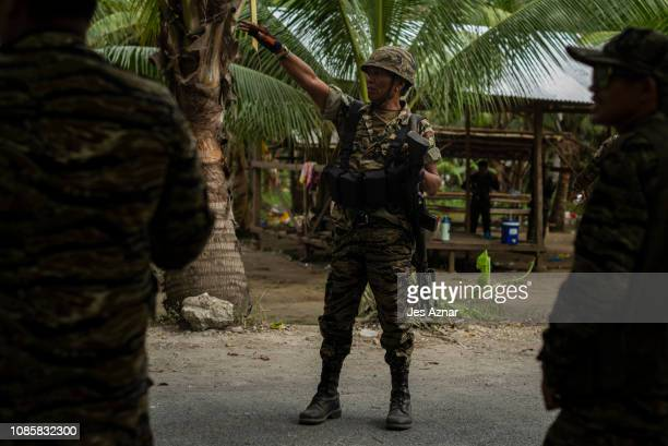 Moro Islamic Liberation Front fighters secure the entrance to their camp as residents cast their votes on January 21, 2019 in MAGUINDANAO, southern...
