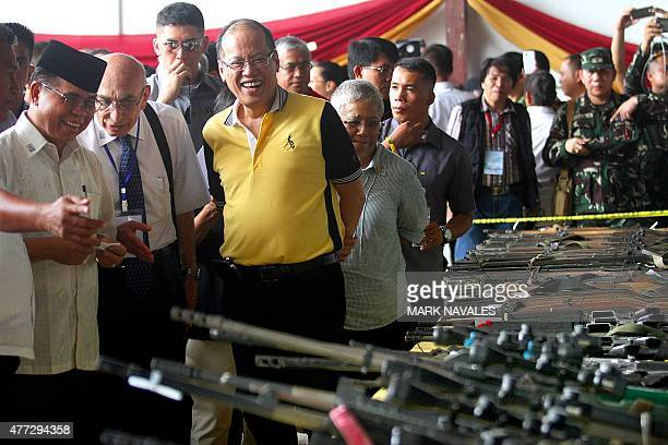 Moro Islamic Liberation Front rebel group chairman Murad Ebrahim and Philippine President Benigno Aquino inspect rebel firearms to be decommissioned...