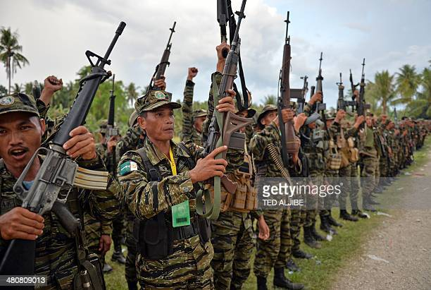 Moro Islamic Liberation Front rebels celebrate the signing of a peace agreement during a rally at Camp Darapanan in the town of Sultan Kudarat on the...