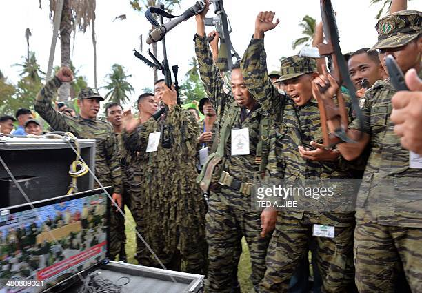 Moro Islamic Liberation Front rebels shout as they watch a live telecast of the signing of a peace agreement during a rally at Camp Darapanan in the...