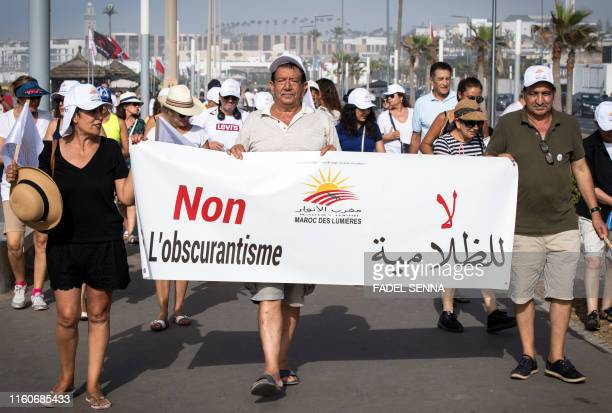 Moroccan activists march behind a large banner reading in Arabic and French no to obscurantism during a demonstration in Casablanca on August 10 2019...