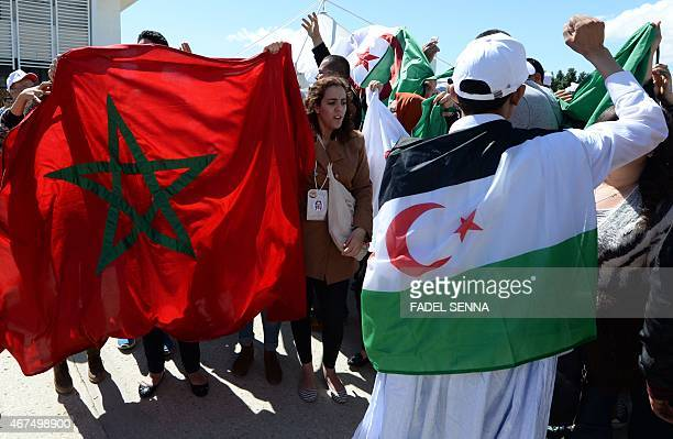 Moroccan activists wave their national flag next to an Algieran man bearing the flag of the Polisario Front seperatist movement as international...