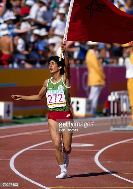 Moroccan athlete Nawal El Moutawakel holds the Morocco flag aloft as she celebrates winning the women's 400 metres hurdles event and the gold medal...