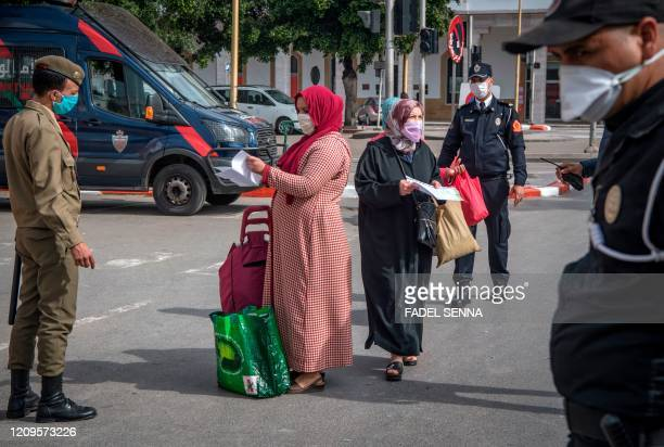 Moroccan authorities wearing protective masks check people at a road block in a street in the capital Rabat on April 9 2020 during the coronavirus...