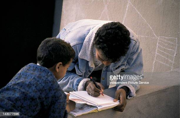 Moroccan boy and young man writing in a notebook Ouarzazate Morocco