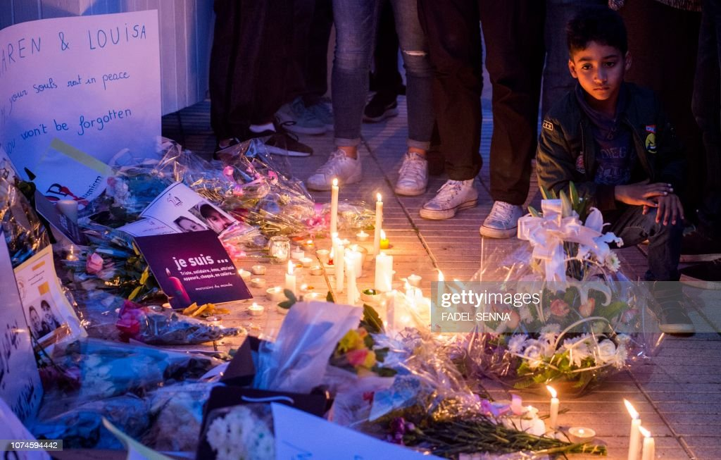 A Moroccan boy looks at candles and flowers during a vigil
