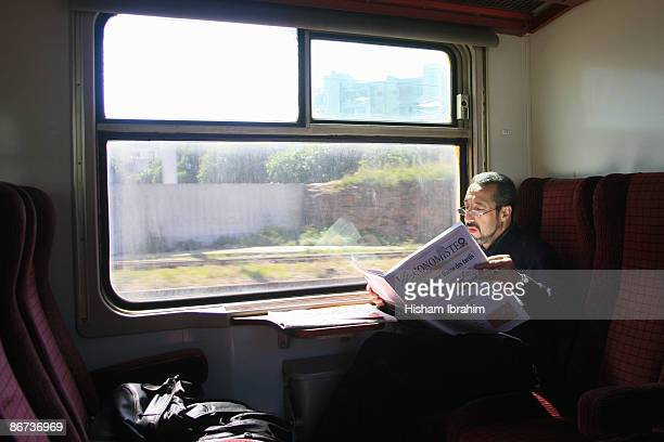 Moroccan Businessman reading newspaper on a train