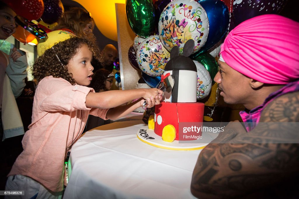 Moroccan Cannon (L) cuts his birthday cake as dad Nick Cannon looks on at Disneyland on April 30, 2017 in Anaheim, California.
