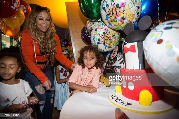 Moroccan Cannon poses next to his birthday cake as mom Mariah Carey looks on at Disneyland on April 30 2017 in Anaheim California