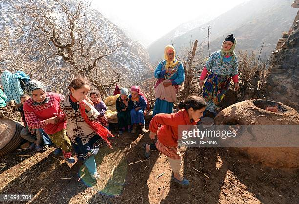 Moroccan children play as women make bread in Taghzirt an isolated village in the elHaouz province in the High Atlas Mountains south of Marrakesh on...