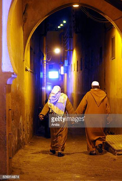 Moroccan couple wearing traditional clothes, holding hands, in a lane of the Old Town, at night, in Marrakech, Morocco.