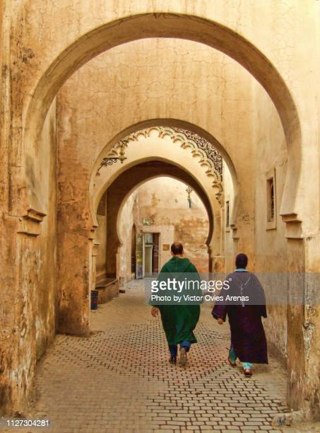 moroccan couple wearing traditional moroccan clothes in an alley of the old medina in marrakech, morocco - victor ovies fotografías e imágenes de stock