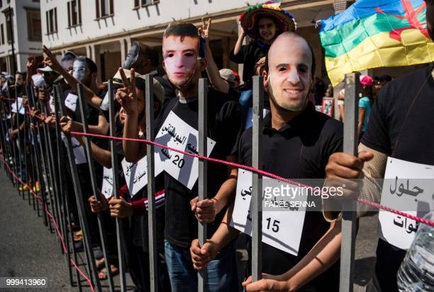 Moroccan demonstrators wear masks showing the faces of AlHirak alShaabi or Popular Movement activists as they stand behind makeshift bars depicting a...