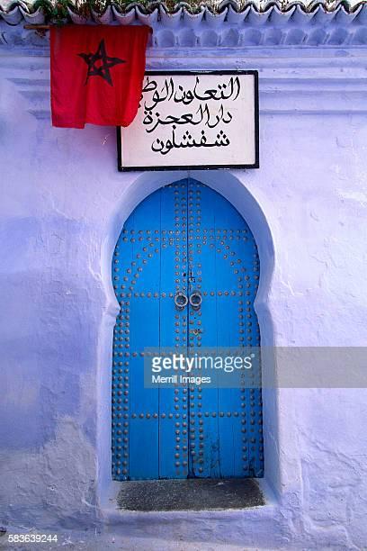 Moroccan Flag Hanging Above Blue Doors