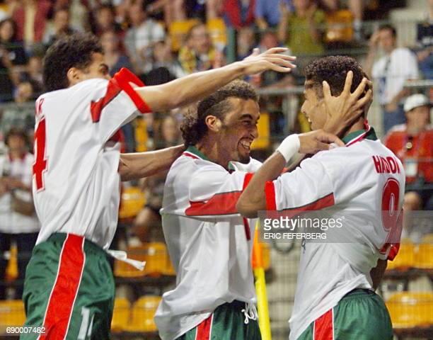 Moroccan forward Abdeljilil Hadda is congratulated by his teammates midfielder Mustapha El Hadji and forward Salaheddine Bassir after scoring 23 June...