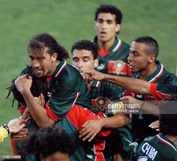 Moroccan forward Moustafa El Hadji is congratulated by his teammates after scoring the first goal 10 June at the Stade de la Mosson in Montpellier...