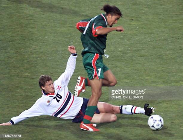 Moroccan forward Moustafa el Hadji jumps to avoid the tackle of Norvegian forward Ole Solskjar 10 June at the Stade de la Mosson in Montpellier...