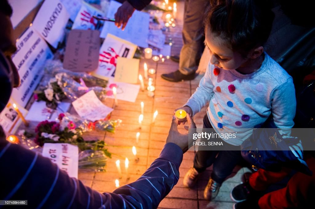 A Moroccan girl places a candle during a vigil for the two    News
