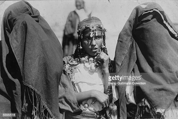 Moroccan girl wearing tribal jewellery between two veiled women in Morocco