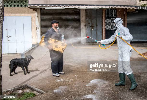 Moroccan health ministry worker disinfects a man walking a dog and carrying a mat in the capital Rabat on March 22, 2020. - A public health state of...