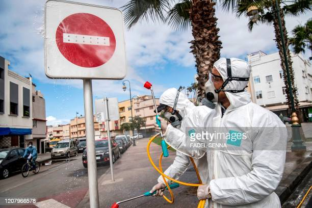 "Moroccan health ministry worker disinfects a ""no entry"" roadsign in the capital Rabat on March 22, 2020. - A public health state of emergency went..."
