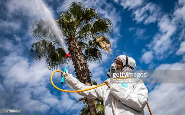 Moroccan health ministry worker disinfects a street in the capital Rabat on March 22, 2020. - A public health state of emergency went into effect in...