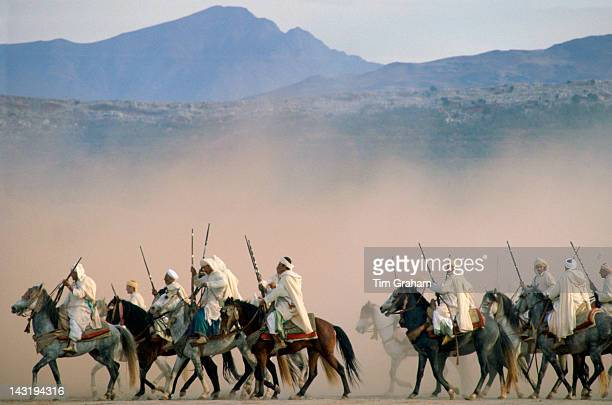 Moroccan horsemen riding in an equestrian Fantasia in desert near Marrakesh Morocco
