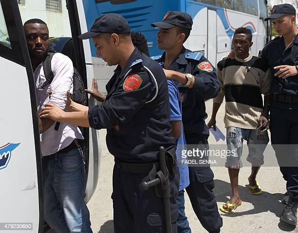 Moroccan immigration officers board migrants into a bus following the eviction of migrants squatting in apartments in the AlIrfane district in...