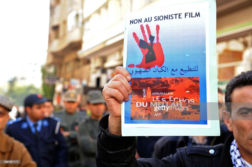 A Moroccan Islamist protestor holds a placard during a demonstration against a documentary movie about the Jews of Morocco by French-Moroccan director Kamal Hachkar on February 5, 2013 outside the cinema Roxy during the Morocco Cinema Festival in Tangiers. There were some 250 thousand Jews in the North African country in the first half of the 20th century. Today the community is big of about 3,000 people.
