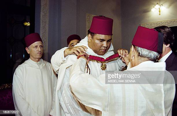 Moroccan King Hassan II decorates former World Heavyweight Champion Muhammad Ali during a ceremony in the Royal Palace in Rabat on January 15 1998...