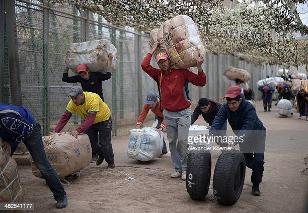 Moroccan labourers carrying goods from Spain to Morocco pass through a checkpoint at the border separating Morocco with the Spanish enclave of...