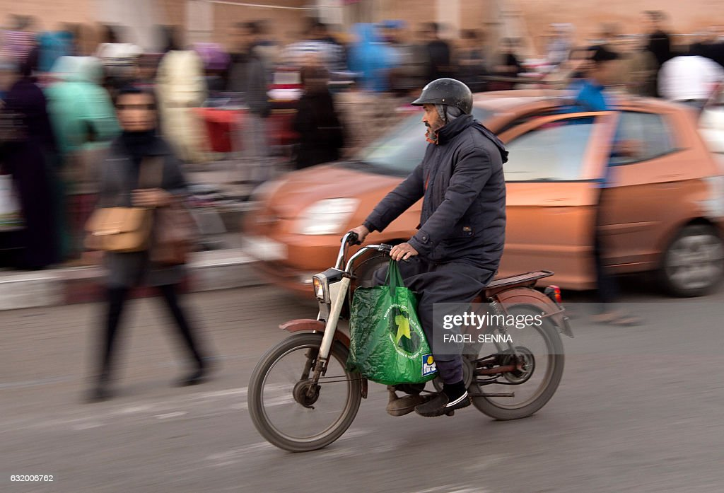 A Moroccan man drives his Peugeot 103 moped in the capital