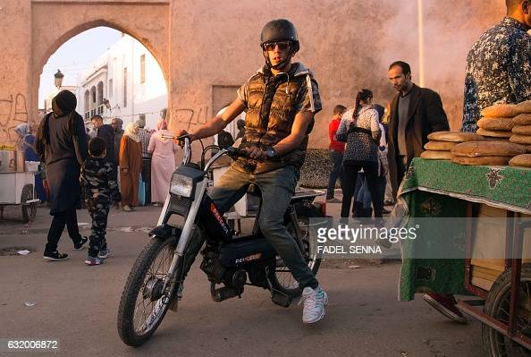 A Moroccan man drives his Peugeot 103 moped through a busy