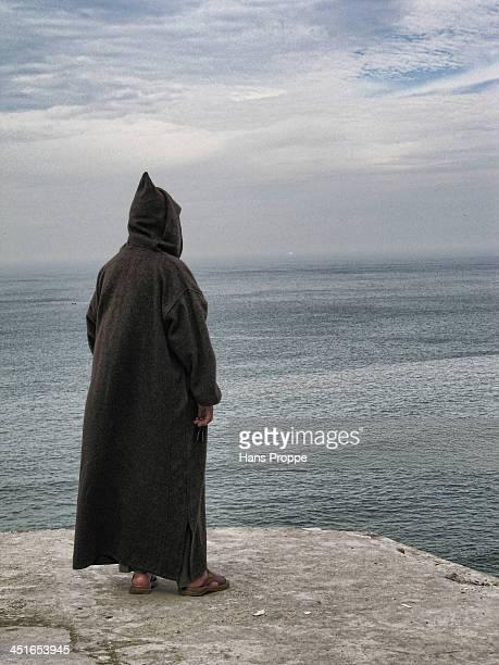 Moroccan man in a djellaba on a rock promontory looking towards Europe.