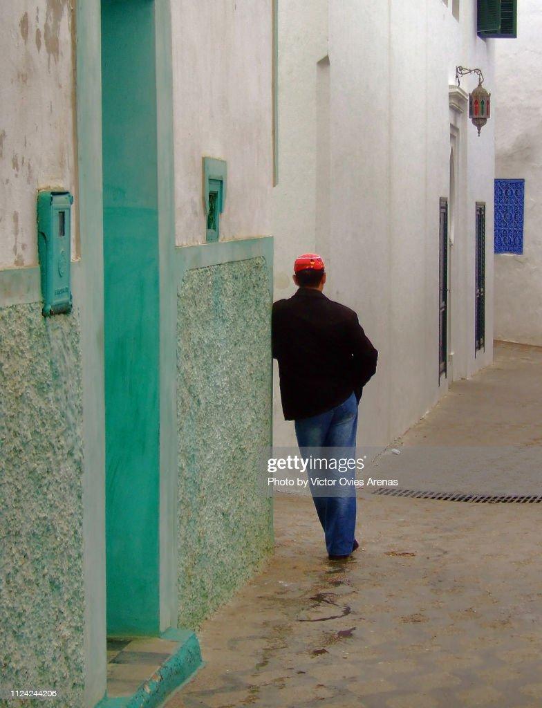 Moroccan man in a narrow street of the medina of Asilah, Morocco : Stock Photo