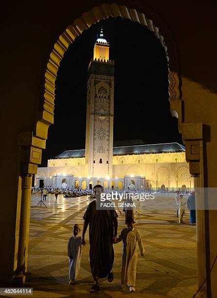 A Moroccan man leaves with his children the Hassan II mosque in Casablanca late on July 24 2014 after attending the Lailat alQadr prayer which falls...