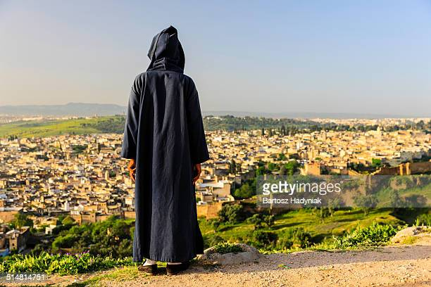moroccan man looking at medina of fez - ceremonial robe stock pictures, royalty-free photos & images
