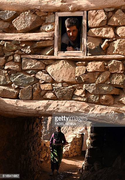 A Moroccan man looks out of a window of a house in Taghzirt an isolated village in the elHaouz province in the High Atlas Mountains south of...