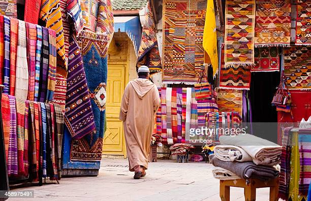 moroccan man passing by the carpet sellers, morocco - souk stock pictures, royalty-free photos & images