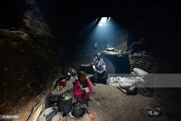 A Moroccan man sits as his daughter makes tea in Taghzirt an isolated village in the elHaouz province in the High Atlas Mountains south of Marrakesh...