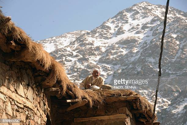 A Moroccan man sits on the roof of his house on the first sunny day after a period of cold weather in Taghzirt an isolated village in the elHaouz...