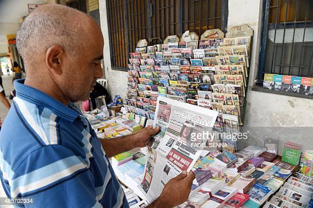 A Moroccan man takes a look at the cover of an issue of Al Ahdath Al Maghribia daily newspaper in Arabic showing portraits of the two French...
