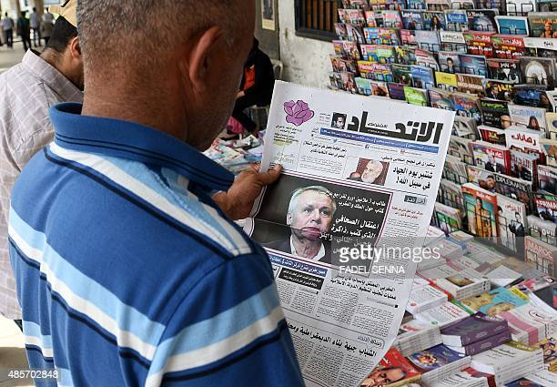 A Moroccan man takes a look at the cover of an issue of AlIttihad daily newspaper in Arabic showing a portrait of Eric Laurent one of the two French...
