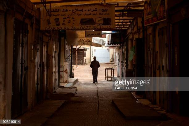 Moroccan man walks through street during a general strike ahead of a demonstration against economic marginalisation on January 19 in the northeastern...
