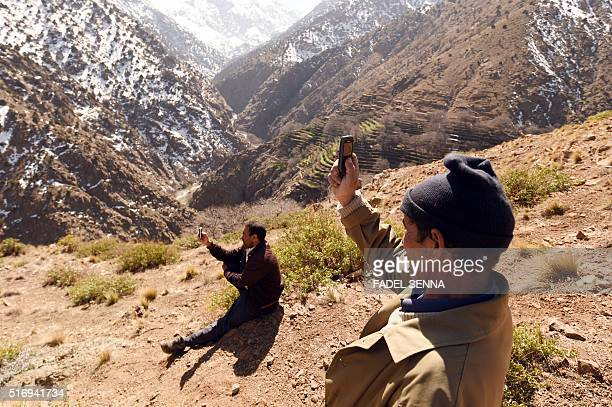 Moroccan men search for mobile signal a few kilometres from Taghzirt an isolated village in the elHaouz province in the High Atlas Mountains south of...