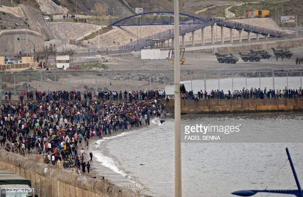 Moroccan migrants rally by a border fence in the northern town of Fnideq in an attempt to cross the border from Morocco to Spain's North African...