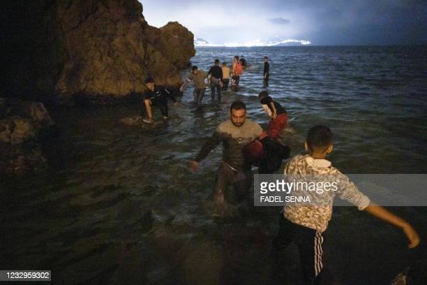 Moroccan migrants walk into shallow waters on the shore of the northern town of Fnideq as they attempt to cross the border from Morocco to Spain's...