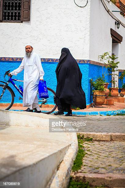 Moroccan muslim family is walking together on the street /la rue Bazzo in Odayah, Rabat, Morocco/ under the sunny light sky, between the blue and...